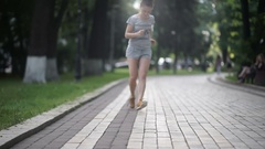 Girl in sneakers run in park and tyes shoelaces Stock Footage