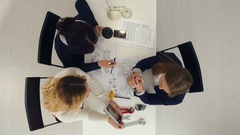 Three female engineers working on plans on tablet at business boardroom table Stock Footage