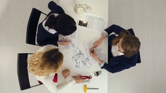 Three female engineers working on plans at business boardroom table Stock Footage