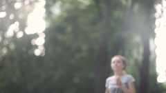 Beautiful curly girl run in the park adn use phone Stock Footage