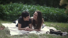 Lesbians relaxing and flirting on grass in park Stock Footage