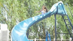 Child on water slide at aquapark. Summer holiday Stock Footage