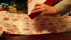 Folding christmas paper over a gift Stock Footage