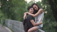 The lesbian sit on a fence and hugs her girlfriend Stock Footage