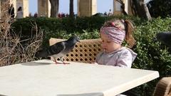 Valletta, Malta - Kid girl feeding street birds pigeons on a cafe table Stock Footage