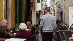 Valletta, Malta - street restaurant tables people sit rest eating and drinking Stock Footage