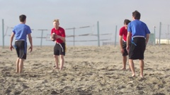 A group of guys playing flag football on the beach, super slow motion. Stock Footage