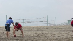 A group of guys playing flag football on the beach, slow motion. Stock Footage