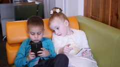 Children boy and girl watch type smart phone cartoon and game app on couch Stock Footage