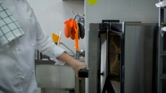 Chef wearing a white uniform opens the oven door pulls out a tray of freshly Stock Footage