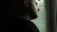 Depressed man smokes looking out the window Stock Footage