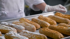Pastry chef, dressed in a white chef's suit and transparent gloves sprinkle with Stock Footage