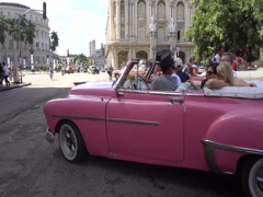Bright pink retro car cabriolet leaves the parking lot on a road Stock Footage