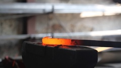 Forging hot metal in smith with hand hummer Stock Footage