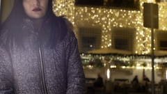 Sad woman looks at the camera, while behind light up the Christmas lights Stock Footage