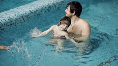 Father and son in the pool. Young Dad teaches his 3-year-old son to swim Arkistovideo