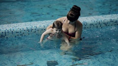 Young parents in the pool teaching his son to swim under water Stock Footage