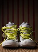 White shoes with lime laces & socks on striped background. Second hand. Stock Photos