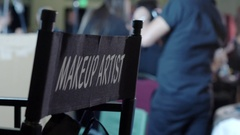 Makeup chair with hairdressers and artists working in background Stock Footage