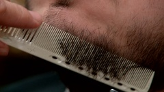 Grooming the beard. Barber cutting hair with a pair of scissors at a barber shop Stock Footage