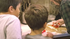 A father and his sons using cookie cutters in the kitchen Stock Footage