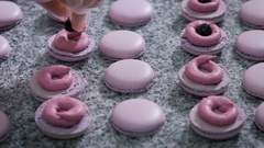 Candy store. Decoration of the French macaroons. The worker of a candy store in Stock Footage
