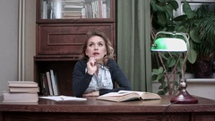Serious woman thinking sittnig at work desk with books Stock Footage