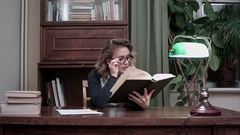 Young smart woman in glasses holding a book and reading enthusiastically Stock Footage