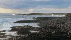 Bright blue waves are breaking of rocky coast of volcanic black beach on south Stock Footage