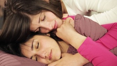 Woman cheering up sad girlfriend in bed Stock Footage