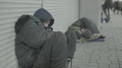 Beggar homeless man sleeps sitting Stock Footage