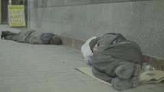 Two beggars, the homeless lying on the floor of the underpass Stock Footage