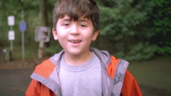 A little boy in a rain jacket running through a park Stock Footage