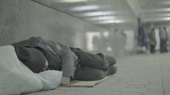 Beggar homeless person sleeps lying on the floor of the underpass Stock Footage