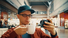 Male traveller in black rim glasses watching video on his mobile phone and Stock Footage