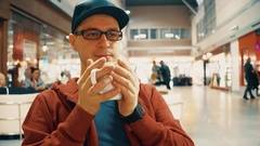 Nerdy man in black rim glasses having big cup of coffee at the airport cafe. 4K Stock Footage