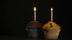 Footage muffins with a candle close up on black background. 4K video Stock Footage