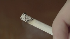 The cigarette slowly smouldering in the hand Stock Footage