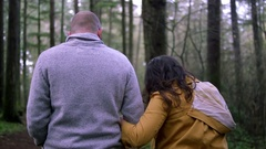 A mother, father, and son holding hands and walking through a forest Stock Footage