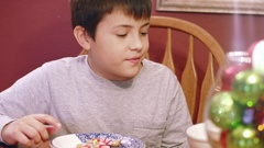 Young boy eating from a bowl of gingerbread cookie decorations Stock Footage