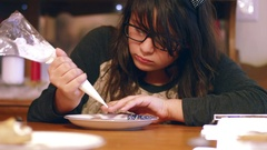 Young girl decorating a gingerbread cookie at table Stock Footage