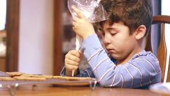 Young boy decorating gingerbread cookie with icing at table Stock Footage
