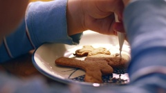 Young boy's hands decorating gingerbread cookie Stock Footage