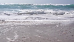 Moderate waves rolling towards a sandy beach Stock Footage