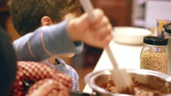 Young boy stirring a pot on stove to melt chocolate chips in kitchen Stock Footage