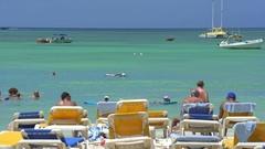 Tourists and deck chairs on tropical beach - Caribbean island, Aruba Stock Footage