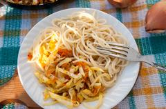 A plate of spaghetti and sauerkraut on a checkered towel Stock Photos