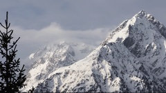 Panorama with clouds waving over snow capped peaks Stock Footage