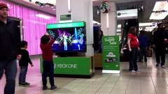 Children dancing with Microsoft demonstrated game beside Microsoft store Stock Footage
