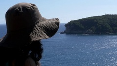 Woman with hat sitting on a high cliff and look at the horizon stretch Stock Footage